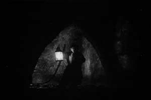 In the dark catacombs a man with a lantern gives the prologue in The Phantom of the Opera, 1925.